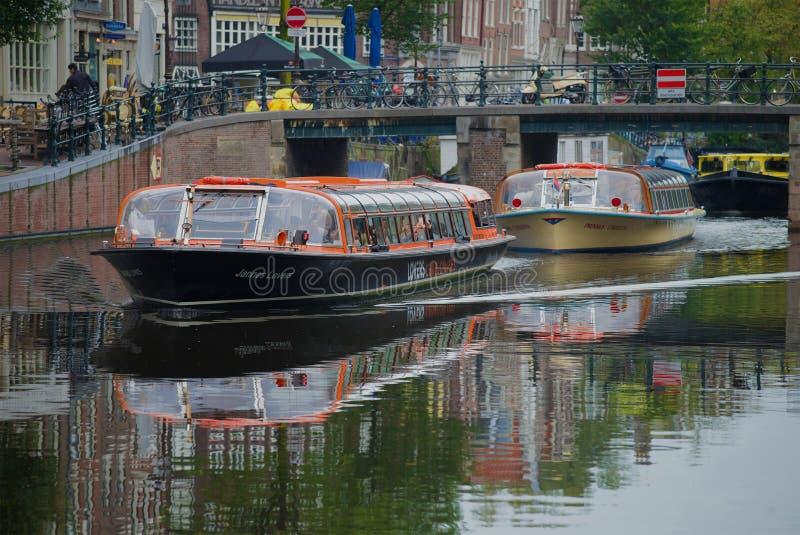 Le navi facenti un giro turistico turistiche del motore passano sotto il ponte della città, Amsterdam immagini stock