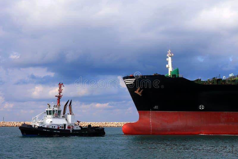 Le navire porte-conteneurs méga de MSC a tiré en un remorqueur images stock