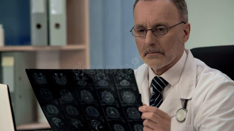 Le neurologue vérifiant l'image IRM, confirme la pathologie dans le cortex cérébral de patients image libre de droits