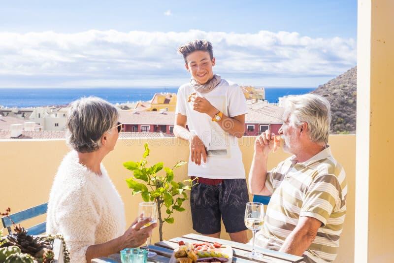 Le neveu adulte mûr de grands-pères et d'adolescent apprécient extérieur dans la terrasse quelques loisirs avec la nourriture et  photographie stock