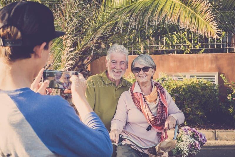 Le neveu d'adolescent prennent une photo utilisant le smartphone à sa pose heureuse de grands-pères avec un vieux vélo de cru Fam images stock