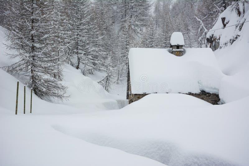 Le nevi copre una casetta della montagna immagini stock