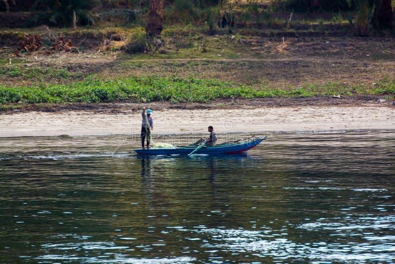 Le Nil, près d'Assouan, le 16 février 2017 : Petit bateau de pêche bleu typique de la rivière avec deux pêcheurs, l'un d'entre eu photos stock