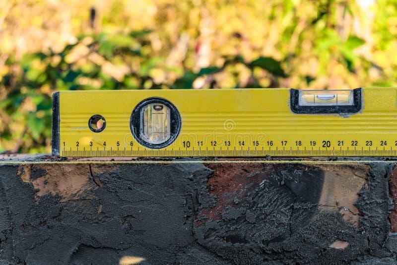Le niveau à bulle jaune se trouve sur le mur de maçonnerie de brique Bulle centrée photo libre de droits