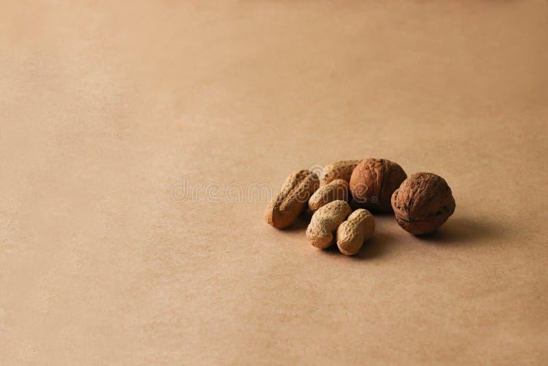 Le nocciole, anacardii, arachidi, noci, mandorle, semi si trovano su un fondo beige immagini stock