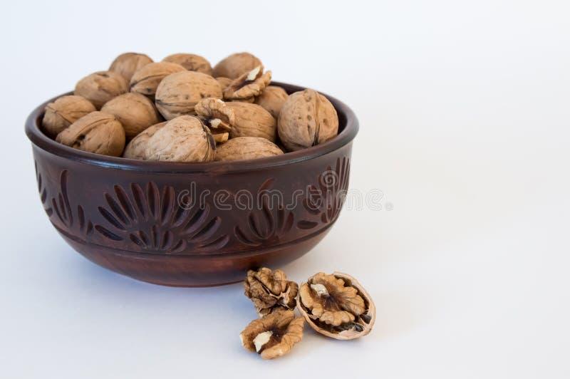 Le noci si trovano in una ciotola, dadi tagliati vicino, su un fondo bianco fotografie stock libere da diritti