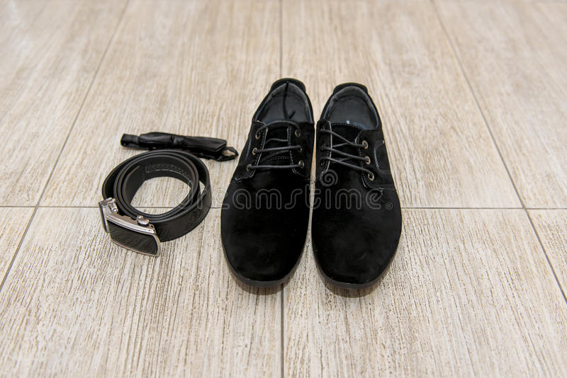 Le noeud papillon noir et les chaussures en cuir toilettent le mensonge à côté de la ceinture des pantalons Accessoires de marié, photos stock