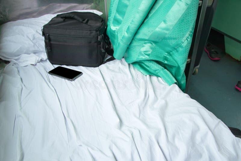 le noir et le téléphone portable de tissu de sac sur le lit blanc dans le train intérieur avec l'espace de copie ajoutent le text photos libres de droits