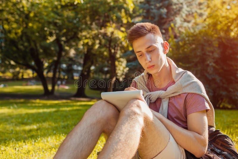 Le note belle di scrittura dell'uomo di istituto universitario in quaderno in città universitaria parcheggiano Studente felice de immagine stock libera da diritti