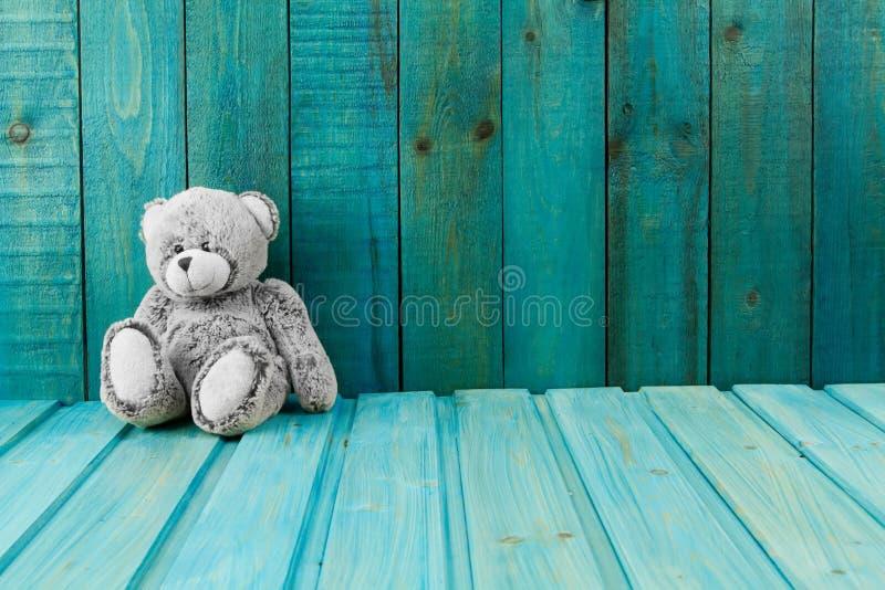 Le nounours concernent le fond en bois de turquoise photographie stock libre de droits