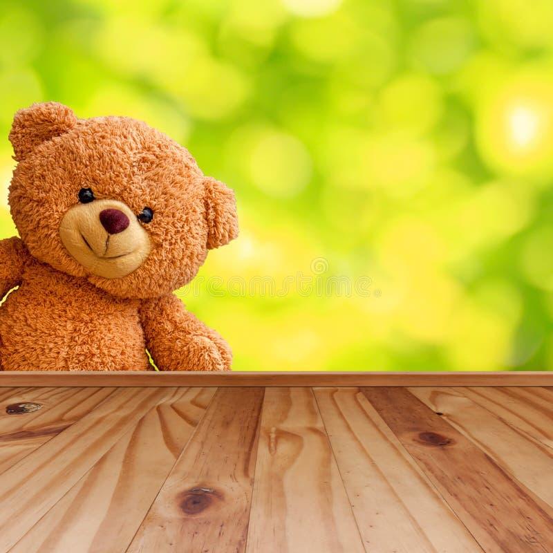 Le nounours concernent le plancher en bois et le fond brouillé photographie stock libre de droits