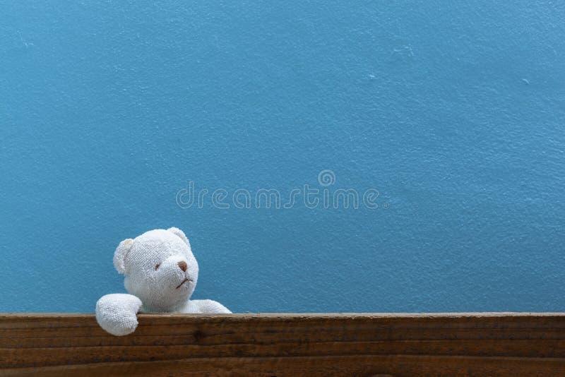 Le nounours concernent le vieux bois à l'arrière-plan bleu avant de mur image stock