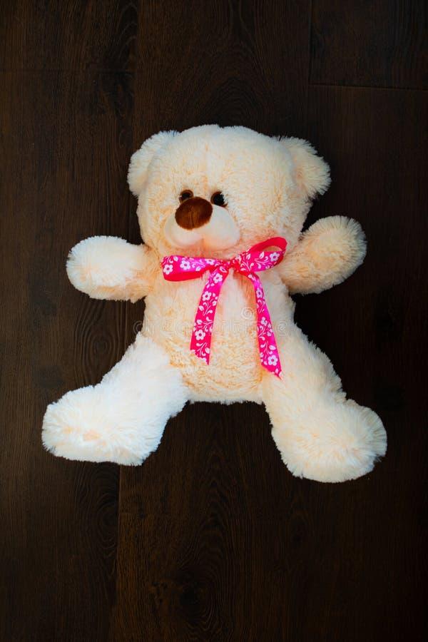 Le nounours mignon concernent le fond en bois Ours de nounours mignon avec un arc rose Un cadeau à l'enfant pour les vacances Cad image stock