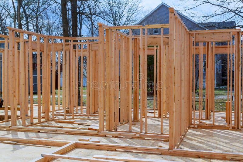 Le nouveau bâton en gros plan a construit à la maison en construction sous le cadre en bois de vue de structure de ciel bleu des  images stock