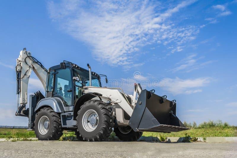 Le nouveau tracteur est sur la route dans la ville, un temps clair avec le ciel bleu photo stock
