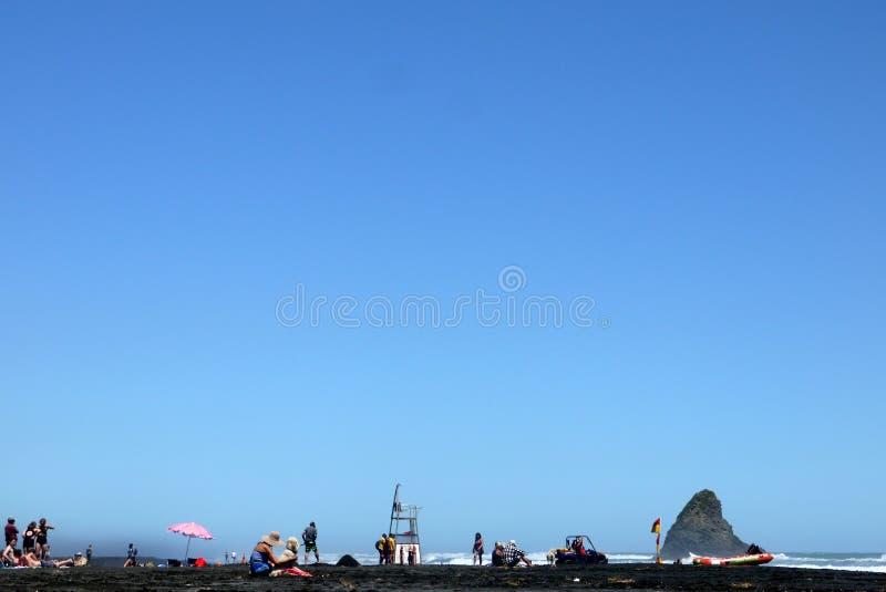 Le Nouvelle-Zélande : vacanciers sur la plage noire de sable images libres de droits