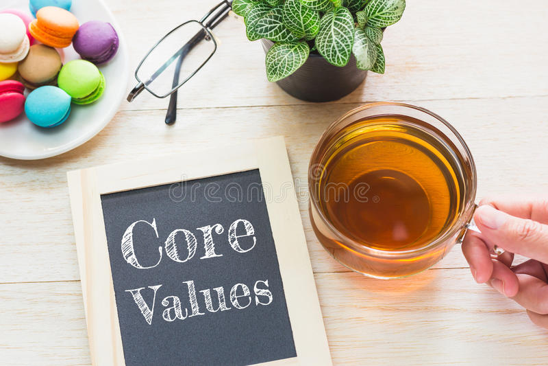 Le noyau de concept évalue le message sur les conseils en bois Macarons et thé en verre sur la table photo libre de droits