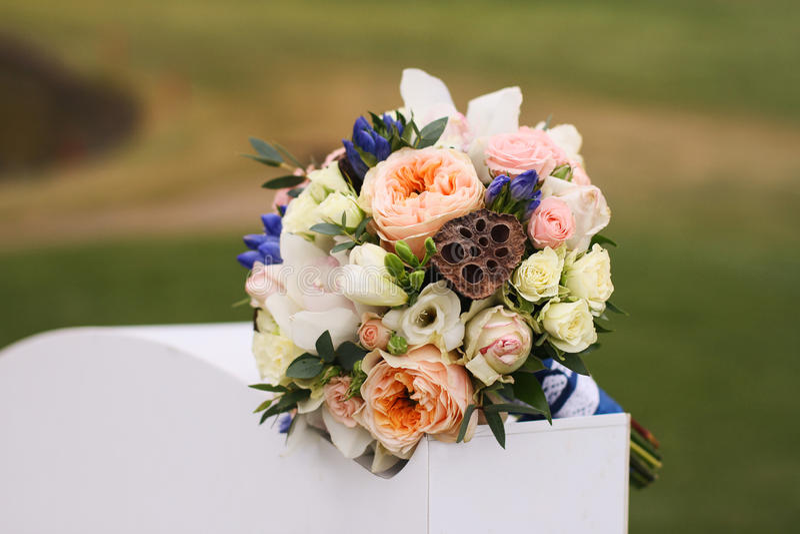 Le nozze fioriscono su un fondo di erba verde su un piedistallo bianco immagine stock libera da diritti