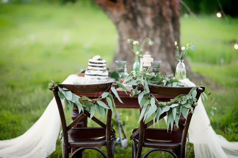 Le nozze hanno decorato la tavola per due con una tovaglia bianca decorata con composizione floreale e un dolce fotografia stock
