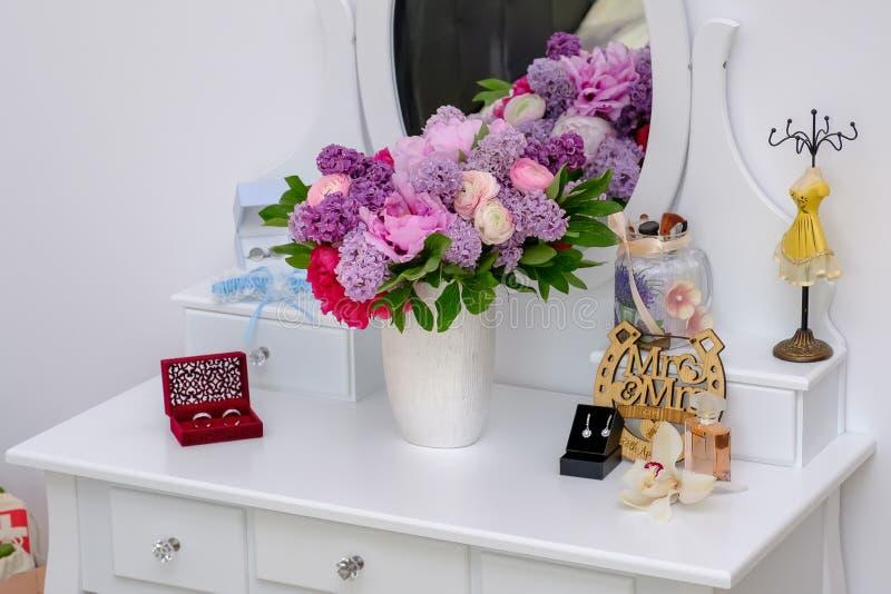Le nozze superbe si rispecchiano con i fiori, le fedi nuziali e l'orecchino naturali della sposa fotografia stock