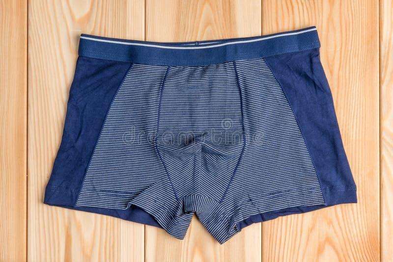 Le nuove mutandine blu del cotone per i vestiti del ragazzo sulla cima dei bordi di legno rivaleggiano immagini stock libere da diritti
