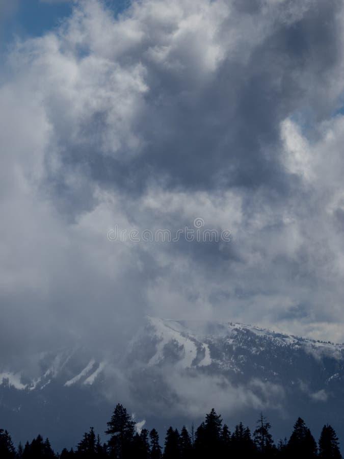 Le nuvole di tempesta oscurano i picchi di montagna fotografie stock