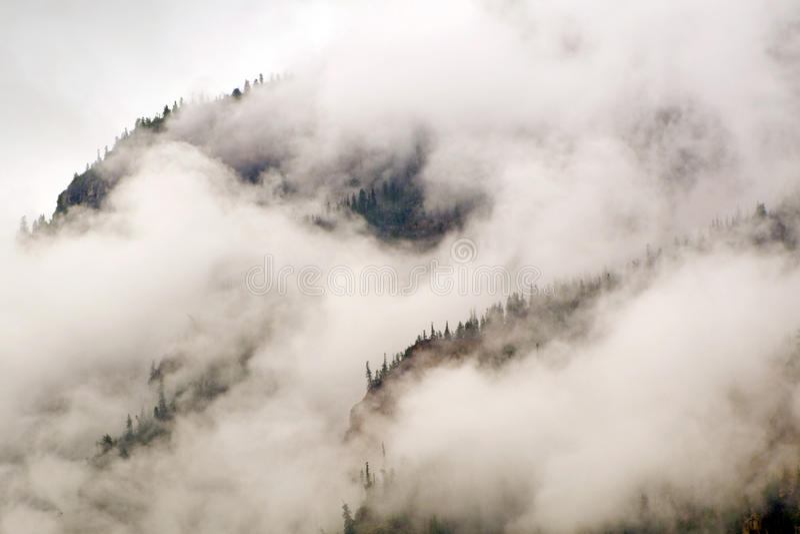 Le nuvole e la nebbia della foschia proteggono questo Colorado Rocky Mountain Bluff Face fotografia stock