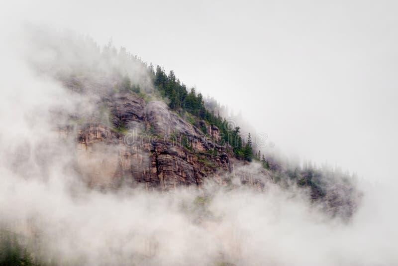 Le nuvole e la nebbia della foschia proteggono questo Colorado Rocky Mountain Bluff Face immagini stock