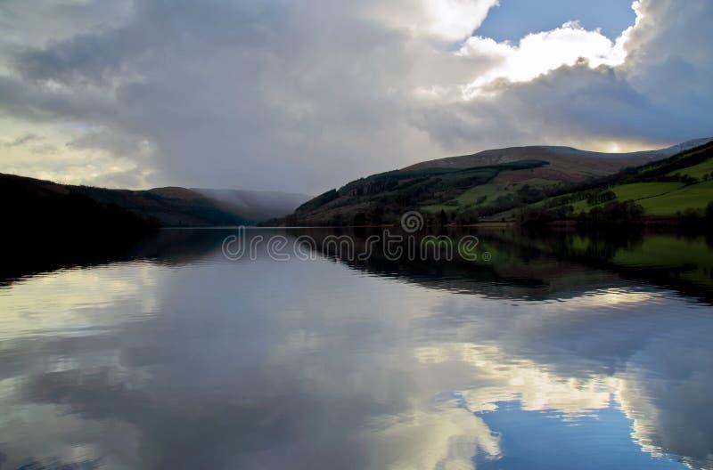 Le nuvole e la neve d'avvicinamento sta cadendo attraverso il bacino idrico di Talybont fotografie stock