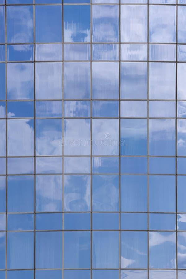 Le nuvole hanno riflesso in finestre dell'edificio per uffici moderno fotografia stock