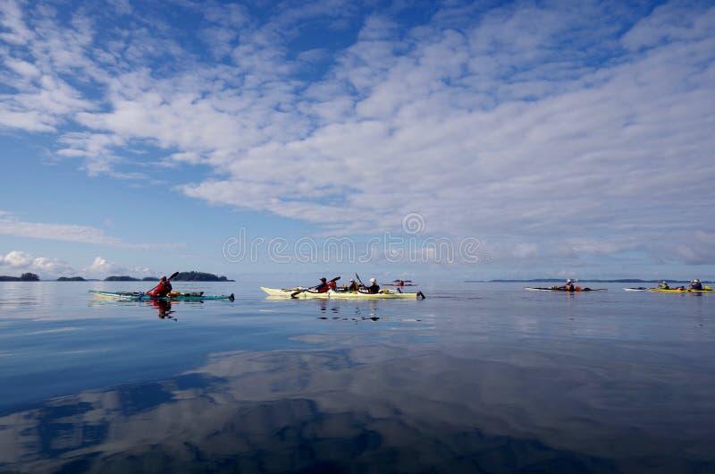 Le nuvole hanno riflesso in oceano vetroso come i kayakers remano nelle isole esterne della foresta pluviale del grande orso del  fotografia stock