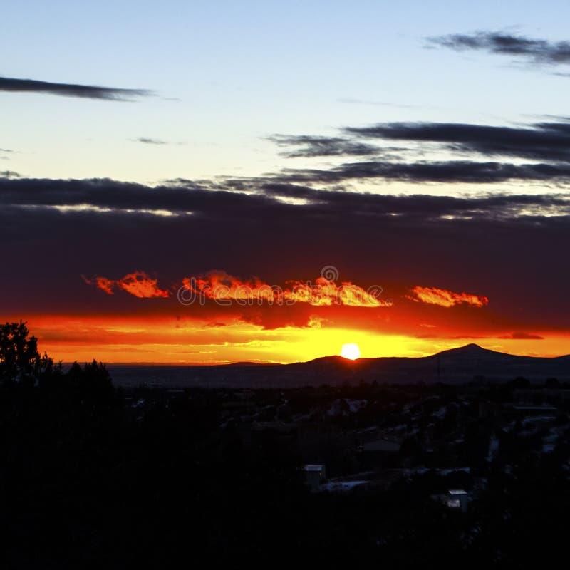 Le nuvole illuminate ballano attraverso il cielo sudoccidentale del tramonto come i fiocchi di fuoco fotografia stock