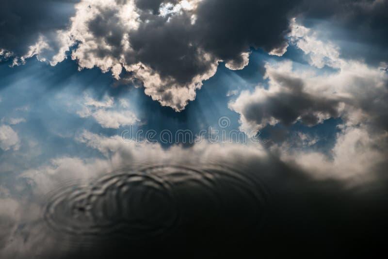 Le nuvole riflettono in acqua immagine stock