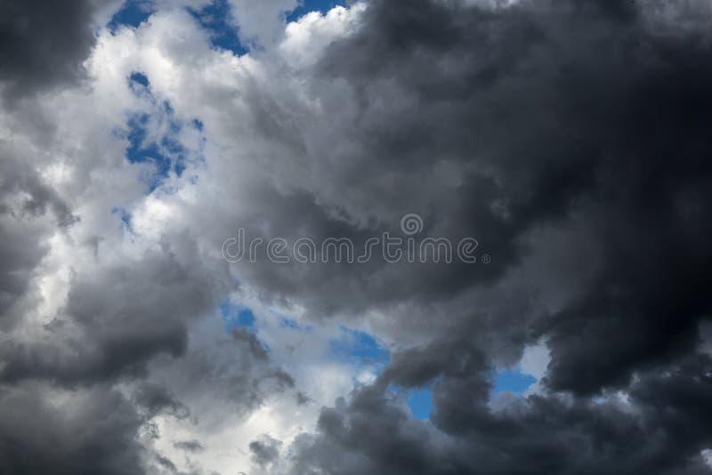 Le nuvole scure e voluminose coprono il cielo blu ` s che va piovere immagini stock