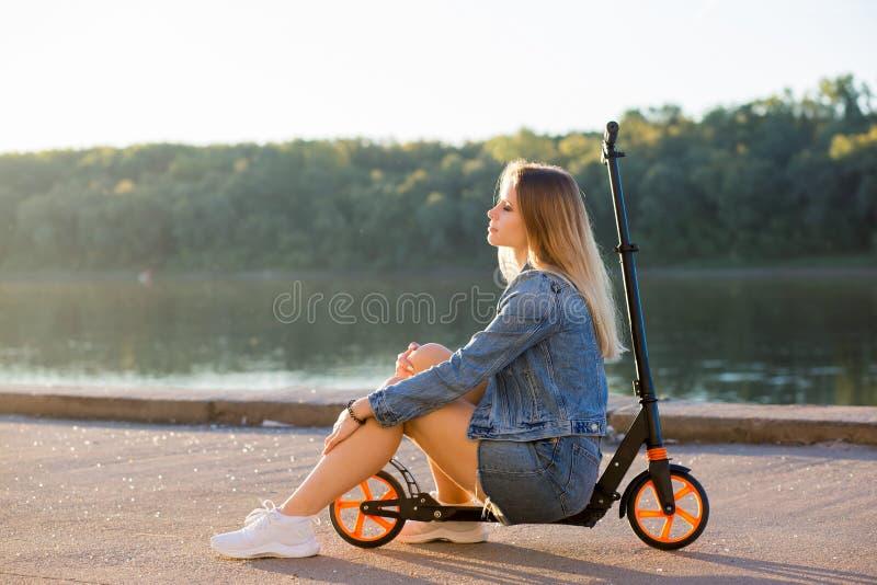 Le och avkopplat kvinnasammanträde på en sparkcykel och vila arkivbild