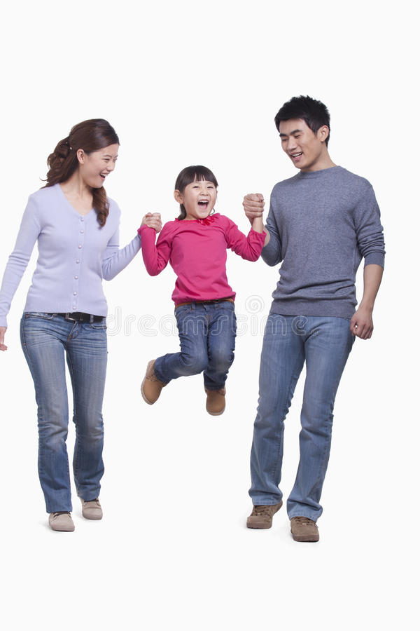 Le och lycklig familj som tycker sig om och att svänga deras dotter i mitt--luft, studioskott arkivbilder