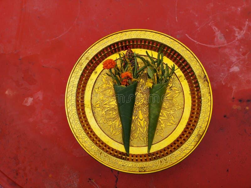Le offerti alla dea, fiori avvolti in foglia della banana hanno offerto a Buddha in piatto dorato con fondo rosso fotografie stock libere da diritti