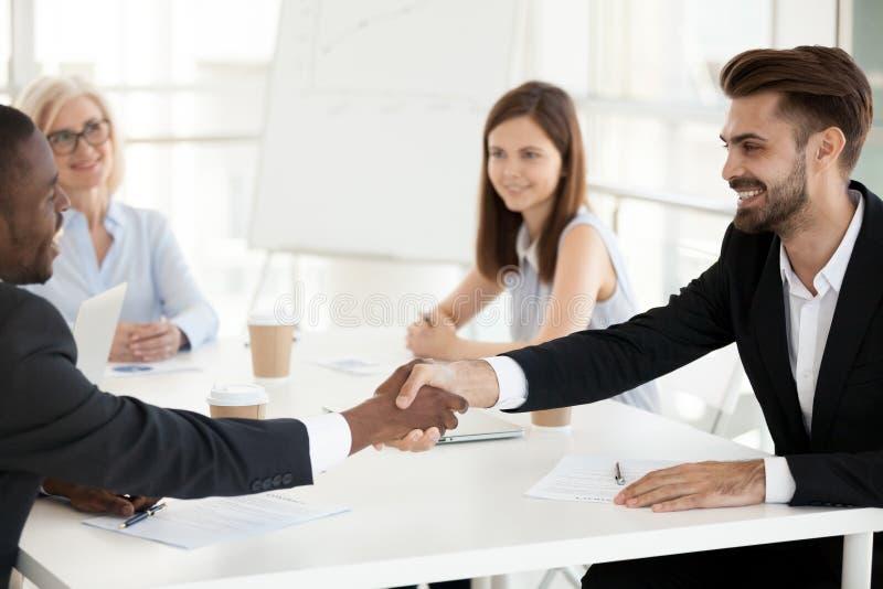 Le olika affärspartners handshaking, stängande avtal arkivbild