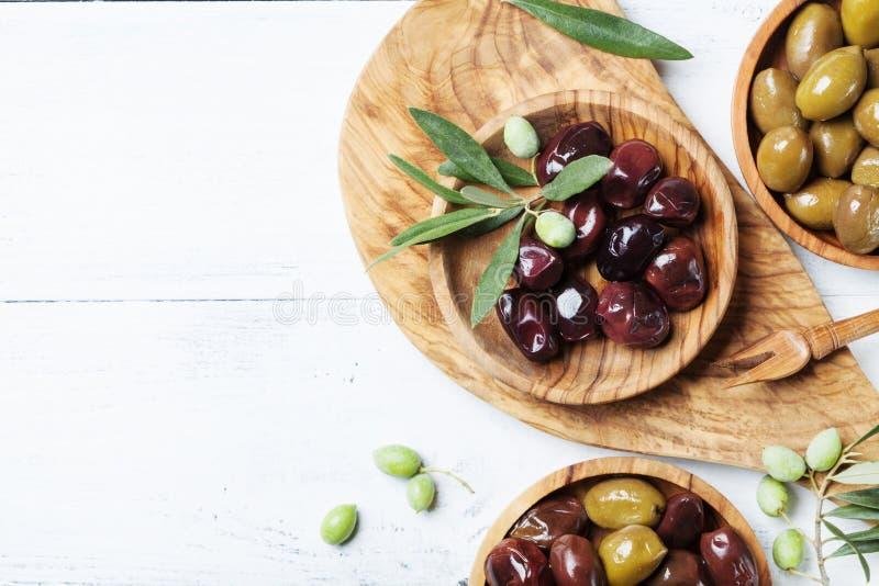 Le olive in ciotole di legno decorate con di olivo fresco si ramificano sulla vista superiore del tavolo da cucina bianco immagine stock libera da diritti