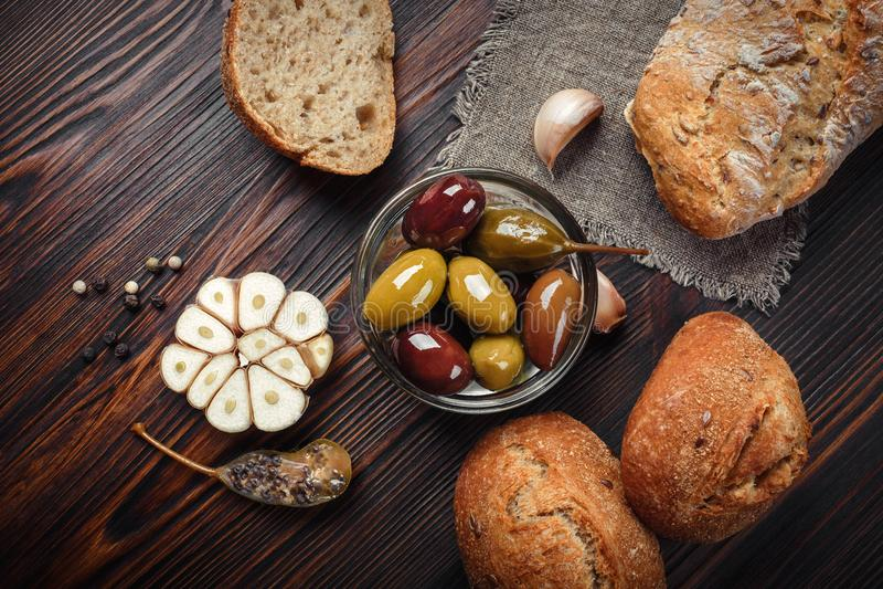 Le olive e l'aglio dei capperi pepano su una tavola di legno fotografie stock