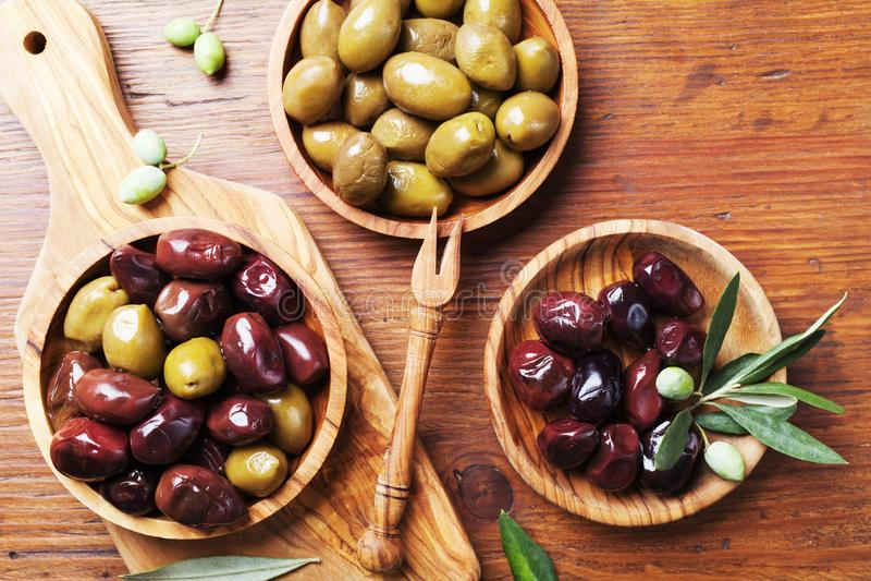 Le olive greche naturali in ciotole con la cucina imbarcano da di olivo da sopra fotografia stock libera da diritti