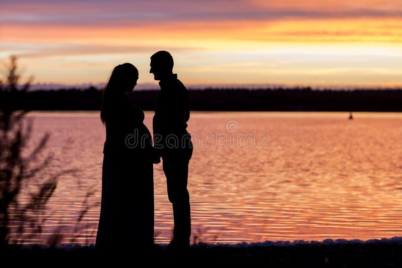 le Ombra-figure dell'uomo e della donna nel ` s del tramonto irradiano fotografia stock