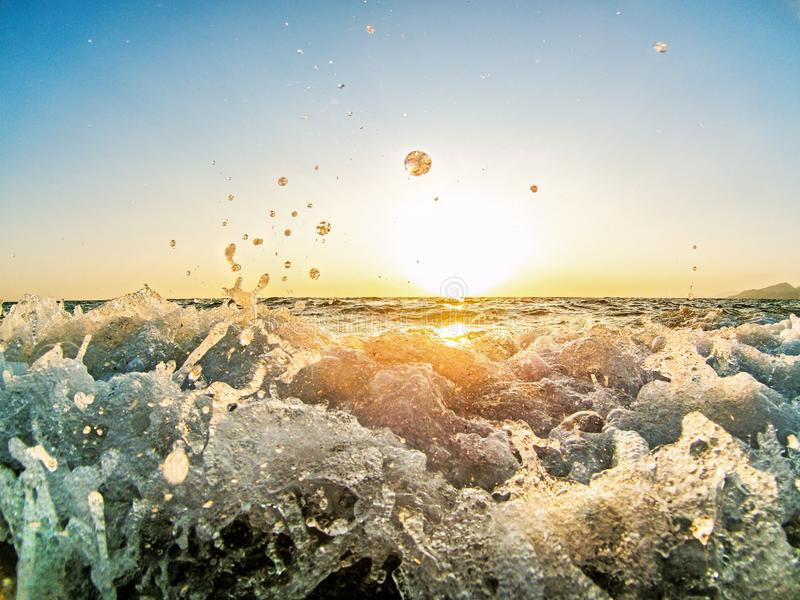Le onde blu luminose del mare sul tramonto nel mare della Grecia con i colori blu piacevoli ed acqua spruzza fotografia stock libera da diritti