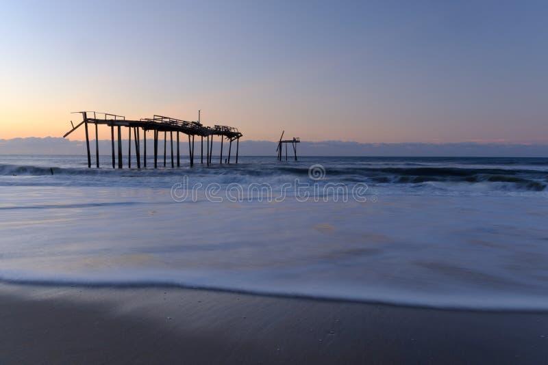 Le onde fresche dell'Oceano Atlantico lavano su vicino ad un pilastro dilapidato fotografia stock