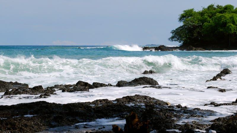 Le onde potenti colpiscono la roccia vulcanica alla spiaggia di Montezuma fotografia stock