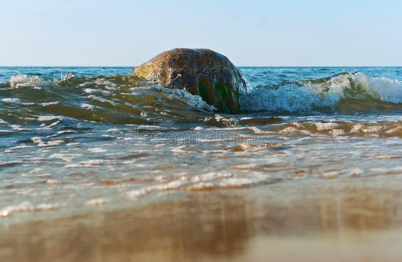 Le onde si rompono sulle rocce costiere, i colpi dell'onda del mare la riva immagine stock libera da diritti