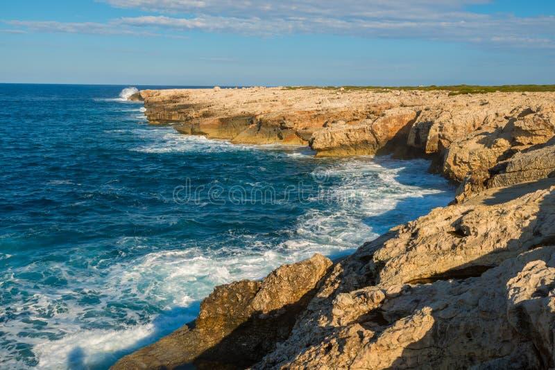 Le onde stanno spruzzando intorno alla riva rocciosa fotografia stock