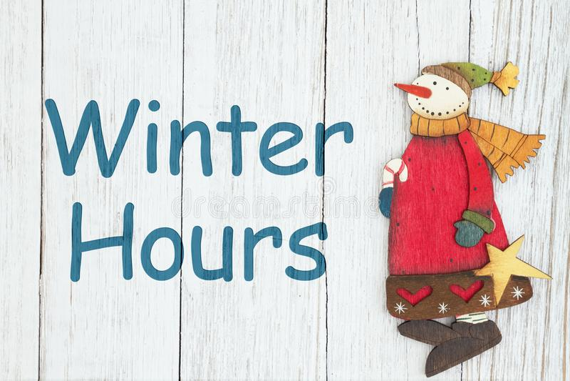 Le ore dell'inverno firmano con il pupazzo di neve fotografia stock