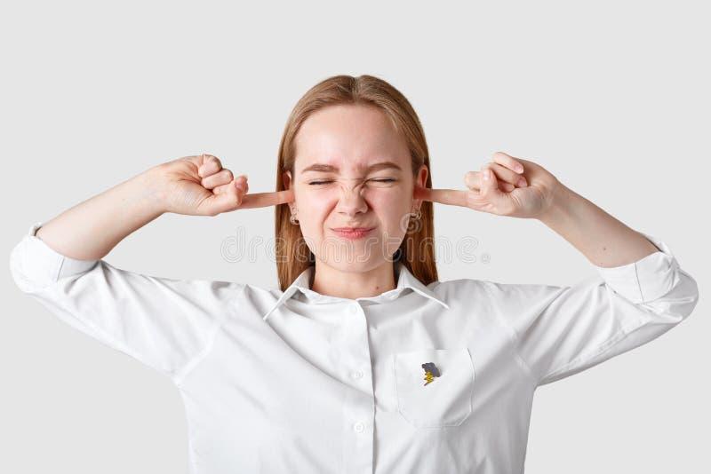 Le orecchie stressanti dei pluggs della donna nella disperazione, aggrotta le sopracciglia fronte con malcontento, trascura la si immagini stock libere da diritti