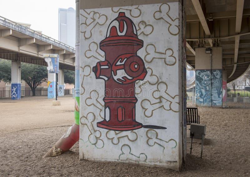 le ossa di cane e dell'Fuoco-idrante in corteccia parcheggiano Ellum centrale e profondo, il Texas immagine stock